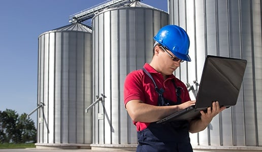 Man working on laptop at agricultural business