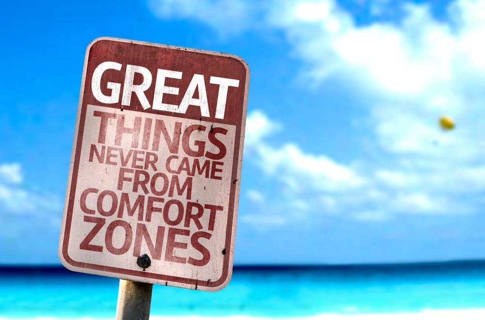 Great Things Never Came From Comfort Zones sign with a beach on background.jpeg